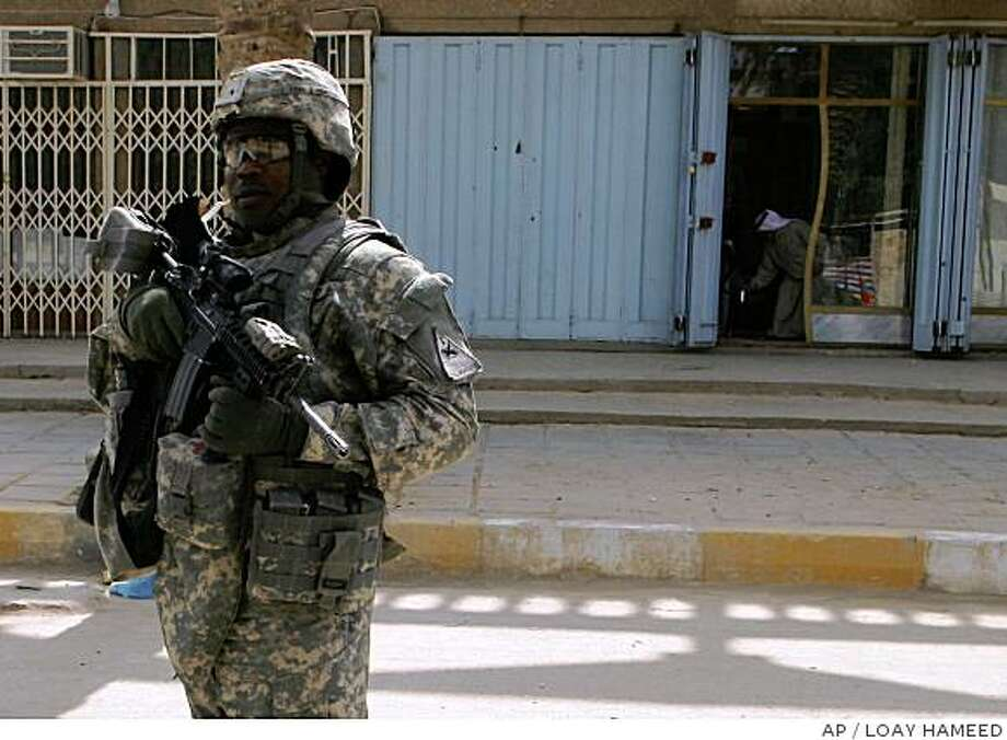 A U.S. Army soldier patrols in Salman Pak, about 15 miles (20 kilometers) south of Baghdad, Iraq, on Monday, June 23, 2008. A disgruntled local official opened fire Monday on American soldiers attending a municipal council meeting in Salman Pak, killing two of them and wounding four other Americans, U.S. and Iraqi officials said. (AP Photo/Loay Hameed) Photo: LOAY HAMEED, AP