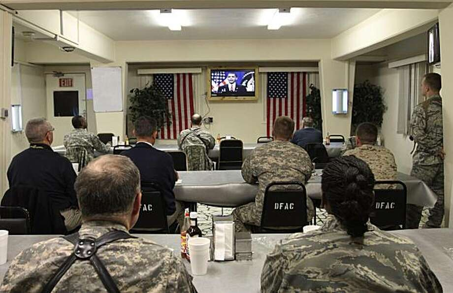 U.S. soldiers and service members listen to U.S. President Barack Obama's speech on TV at the U.S. Camp Eggers in Kabul, Afghanistan, Wednesday, Dec. 2, 2009. (AP Photo/Musadeq Sadeq) Photo: Musadeq Sadeq, AP