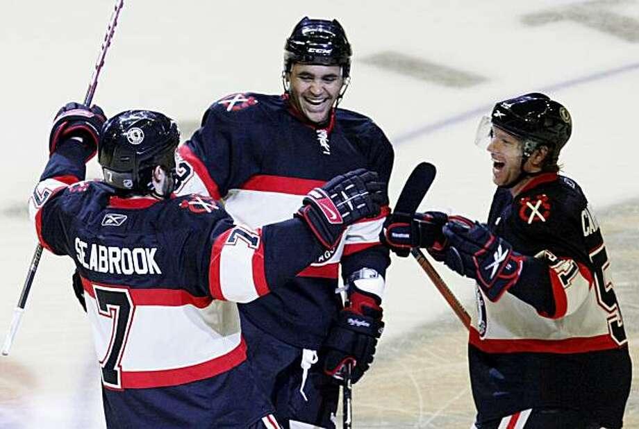 Chicago Blackhawks defenseman Brent Seabrook, left, celebrates his game winning overtime shootout goal with teammates Dustin Byfuglien, center and Brian Campbell during an NHL hockey game and 4-3 win over the Columbus Blue Jackets Tuesday, Dec. 1, 2009 in Chicago. (AP Photo/Charles Rex Arbogast) Photo: Charles Rex Arbogast, AP