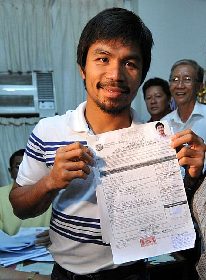 Philippine boxing icon Manny Pacquiao (L) poses with his Certificate of Candidacy (CoC) after filing at the provincial office of the Commisssion on Elections (COMELEC) in the town of Alabel, in Saragani province, on December 1, 2009. Pacquiao is running for a seat in congress representing a district in the southern Philippines in the May 10, 2010 elections.  AFP PHOTO/TED ALJIBE (Photo credit should read TED ALJIBE/AFP/Getty Images) Photo: TED ALJIBE, AFP/Getty Images