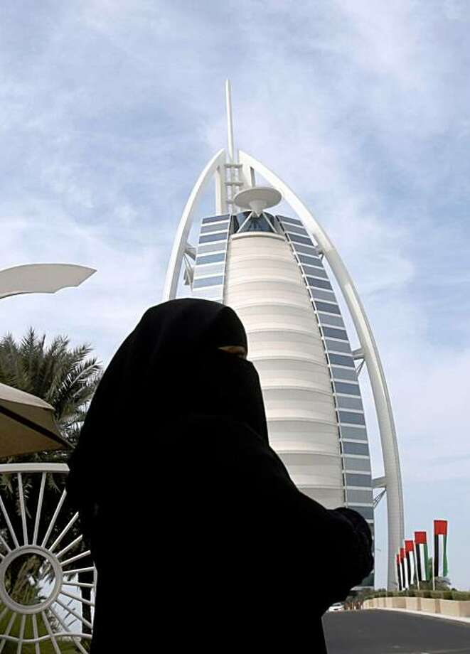 An Emirati woman walks past the Burj Al-Arab hotel in the Gulf emirate of Dubai on November 29, 2009. Dubai's shock alert of possible debt default will send Gulf markets, mainly in Dubai and Abu Dhabi, plunging when they resume trading this week after a holiday weekend, economists predicted. AFP PHOTO/KARIM SAHIB (Photo credit should read KARIM SAHIB/AFP/Getty Images) Photo: Karim Sahib, AFP/Getty Images