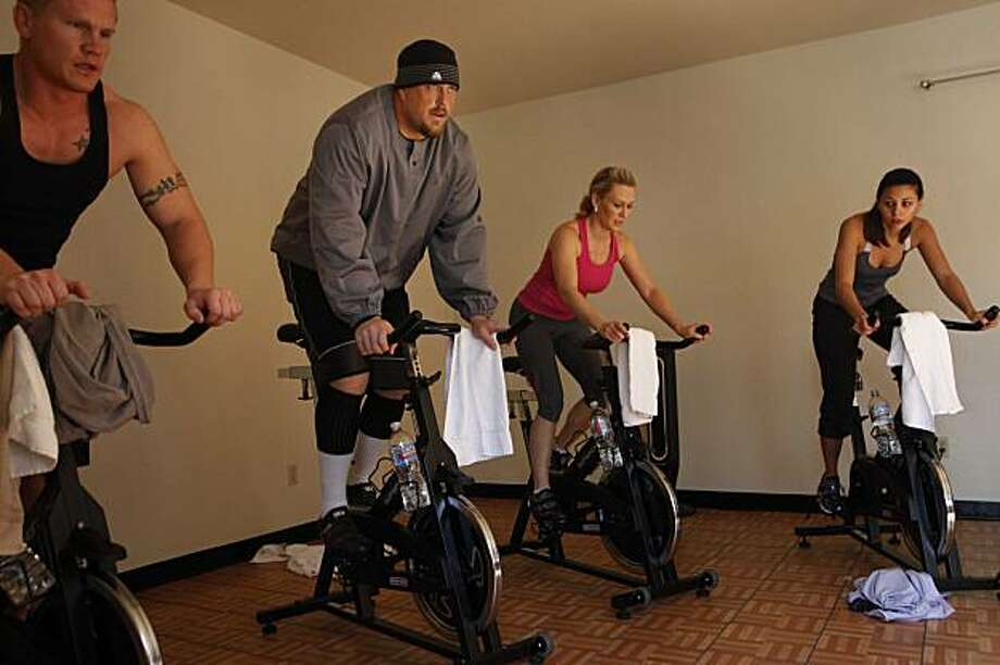 On his day off from NFL duties, San Francisco 49ers lineman Barry Sims (lft Hat) works out next to his wife Shae Sims (pink) during spin class at IM=X pilates studio on Tuesday Dec. 1, 2009 in Danville, Calif. Photo: Mike Kepka, The Chronicle