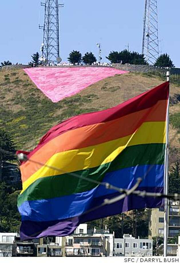 A pink triangle sits on top of Twin Peaks above the rainbow flag flying in the Castro district in San Francisco. The pink triangle symbol (now a symbol of pride) was once used by Nazis in concentration camps to identify and shame homosexuals. The two symbols mark the eve of the Gay Pride celebration for San Francisco. 6/28/03 in San Francisco. DARRYL BUSH / The Chronicle Photo: DARRYL BUSH, SFC