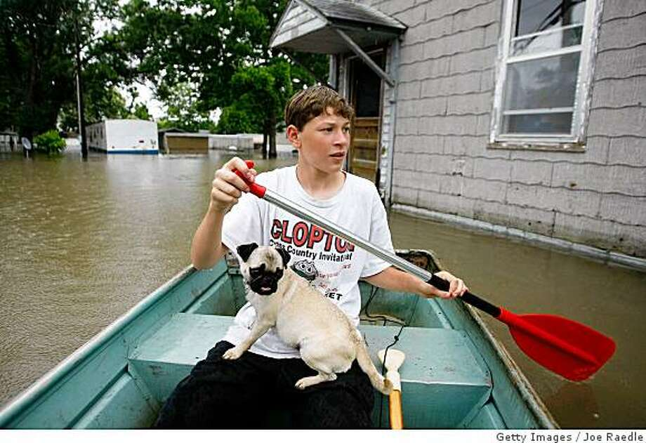 CLARKSVILLE, MO- JUNE 20: Dalton Myers,15, with his dog Cricket negotiates his boat through the flood waters from the Mississippi River that inundate his neighborhood June 20, 2008 in Clarksville, Missouri.  People along the river continued to deal with the high waters.  (Photo by Joe Raedle/Getty Images) Photo: Getty Images