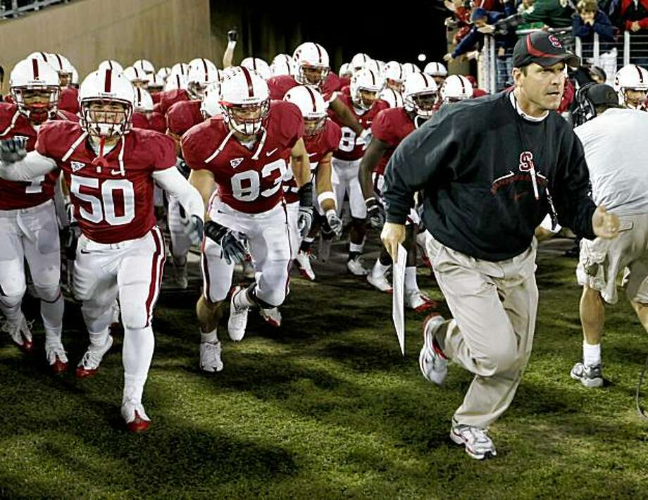 Stanford head coach Jim Harbaugh right runs with the team before their game against Notre Dame on Saturday. Photo: Paul Sakuma, AP