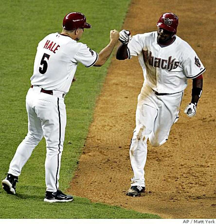 Arizona Diamondbacks' Justin Upton high-fives third base coach Chip Hale (5) after hitting a solo home run against the Oakland Athletics during the eighth inning of a baseball game Thursday, June 19, 2008, in Phoenix. (AP Photo/Matt York) Photo: Matt York, AP