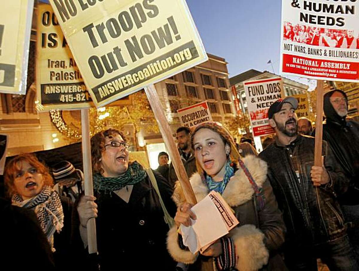 Protesters like Desiree Aubry (right center) attended the first anti-war protest since the Obama speach. About two hundred people against the President's policies in Afghanistan and actions in the Middle East held a rally at Powell and Market Streets and marched around the area Wednesday December 2, 2009.