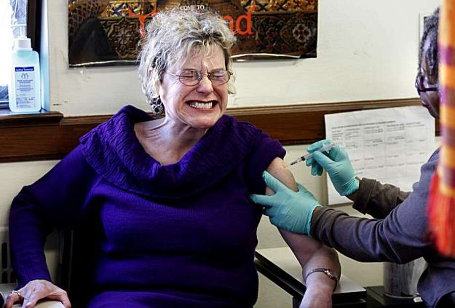 Lisa Watson RN (far right) gives a standard flu shot to Carolyn Eder of San Francisco who was glad they were available. The standard flu shots are still being given out at Dept. of Health in San Francisco on a daily basis. Photo: Brant Ward, The Chronicle