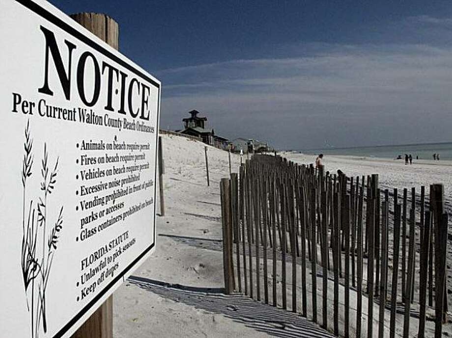In a  Tuesday, Nov. 24, 2009 photo, a notice is posted on the beach at Gulf Islands National Seashore, Fla. The Florida Supreme Court will hear argument on Wednesday Dec. 2, 2009 on whether a nearly seven-mile stretch of beach in the Florida Panhandle is public or private after the state poured sand on eroding shores.(AP Photo/Melissa Nelson) Photo: Melissa Nelson, AP