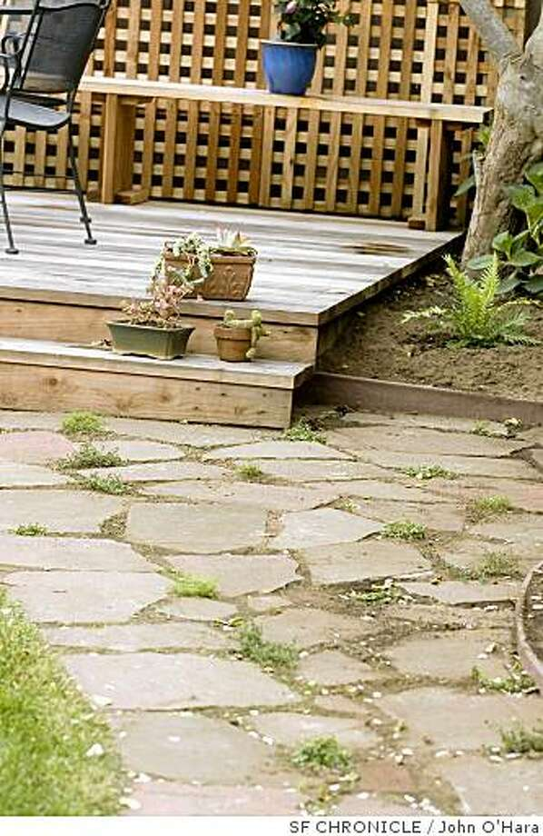 Paul Kilduff residence, San Francisco. A detached deck. 11x18 feet, in a back yard that is approx 40X60 ft. Pavers on the ground were from old existing cement in rear yard. Alica Kilduff 5 yrs. waters plants. Photo: John O'Hara, SF CHRONICLE