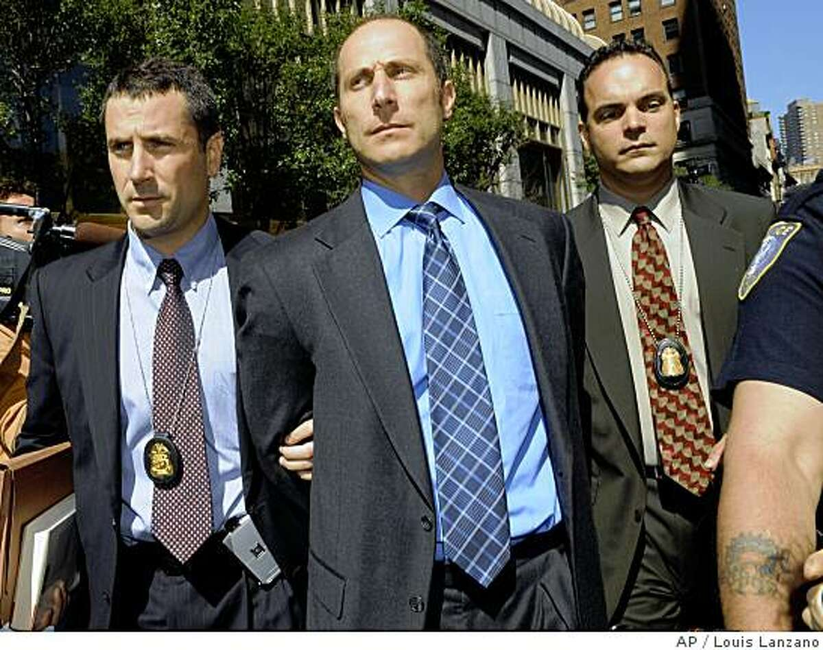 Federal agents exit 26 Federal Plaza with handcuffed former Bear Stearns hedge fund manager Matthew Tannin, Thursday, June 19, 2008, in New York. Indictments will be handed down on Tannin and ex-manager Ralph Cioffi, both accused of securities fraud in the wake of the collapse of the subprime mortgage market which foreshadowed Bear Stearns' own demise. (AP Photo/ Louis Lanzano)