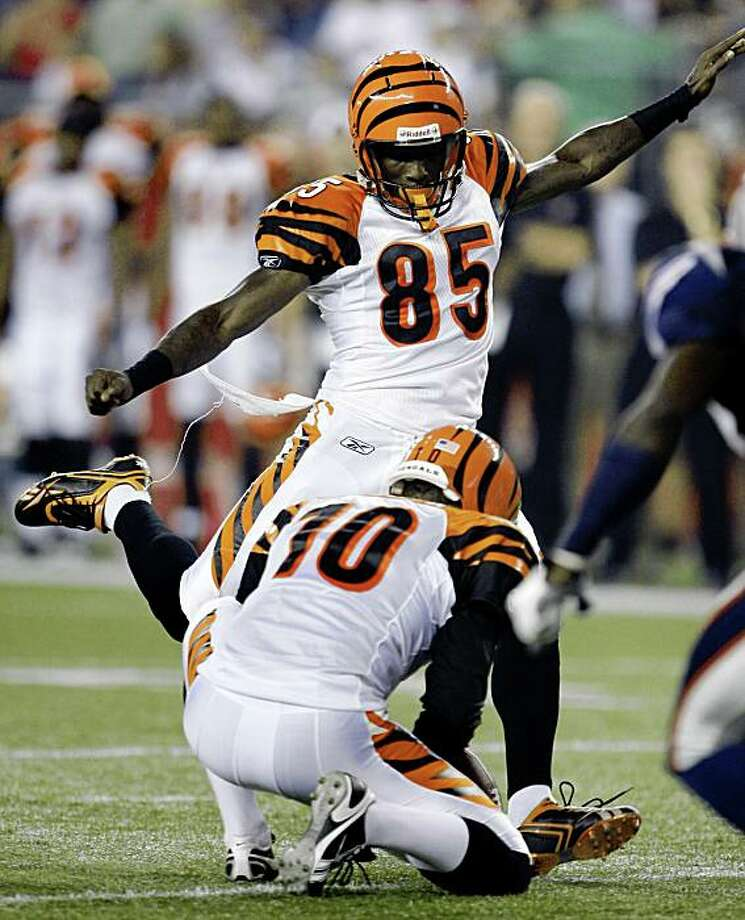 Cincinnati Bengals wide receiver Chad Ochocinco (85) kicks the extra point after a touchdown by teammate Chris Henry in the second quarter of their preseason NFL football game in Foxborough, Mass., Thursday Aug. 20, 2009. Holding is punter Kevin Huber. (AP Photo/Charles Krupa) Photo: Charles Krupa, AP