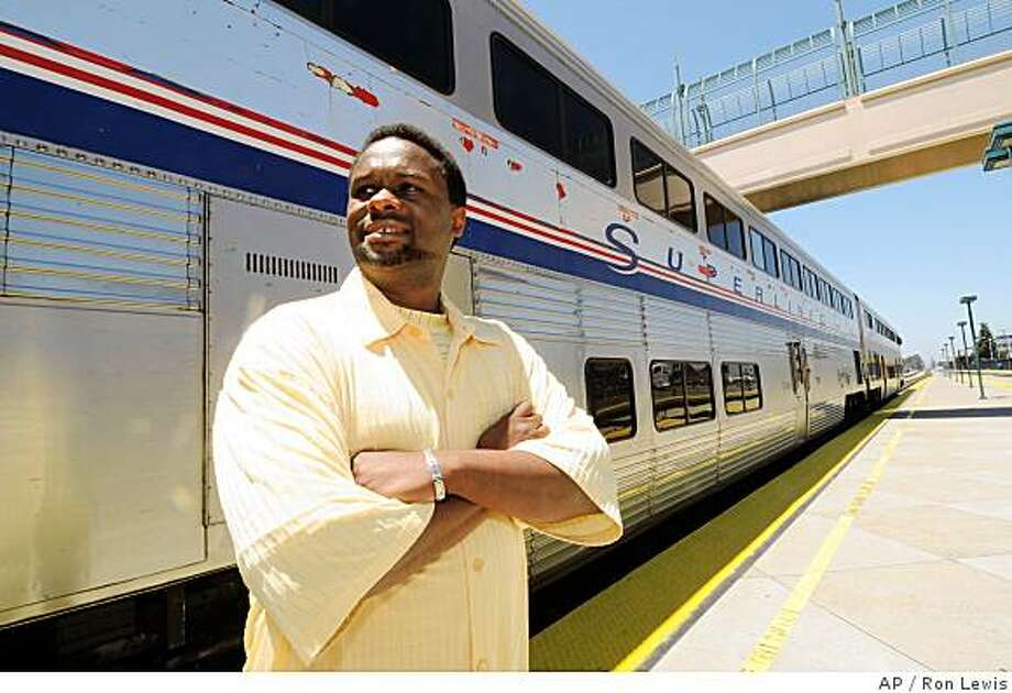 Demetrius Stroud stands near a Northbound Amtrak train at the Emeryville, Calif., train station Tuesday, June 17, 2008. Because of high gasoline prices, Stroud is purchasing a home near the the Elk Grove, Calif., Amtrak station and will soon commute by train between the Sacramento area and Emeryville rather then drive. (photo by Ron Lewis) Photo: Ron Lewis, AP