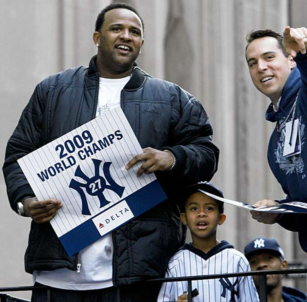 New York Yankees first baseman Mark Teixeira, right, points out something to pitcher CC Sabathia, left, as the pair ride on a float with Sabathia's son CC III during a ticker-tape parade along Broadway celebrating their 27th World Series championship on Friday, Nov. 6, 2009, in New York. (AP Photo/Kathy Willens)