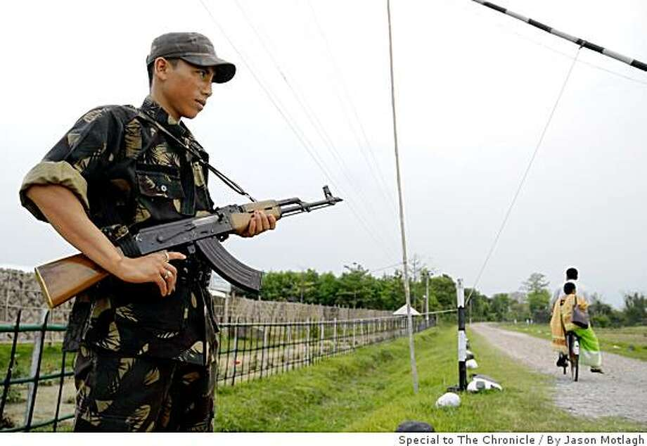A rebel soldier guards the main gate of one of three camps designated for fighters of the National Democratic Front of Boroland  after a 2005 ceasefire agreement with the Indian government. The camp is located near the town of Udalguri in the northeastern state of Assam. Photo: By Jason Motlagh, Special To The Chronicle