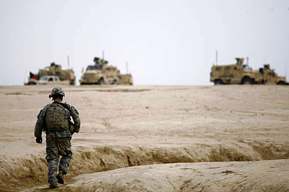 A U.S. Army soldier returns to the vehicles after a dismounted patrol near the town of Baraki Barak, Logar province, Afghanistan, Monday, Nov. 23, 2009. (AP Photo/Dario Lopez-Mills) Photo: Dario Lopez-Mills, AP
