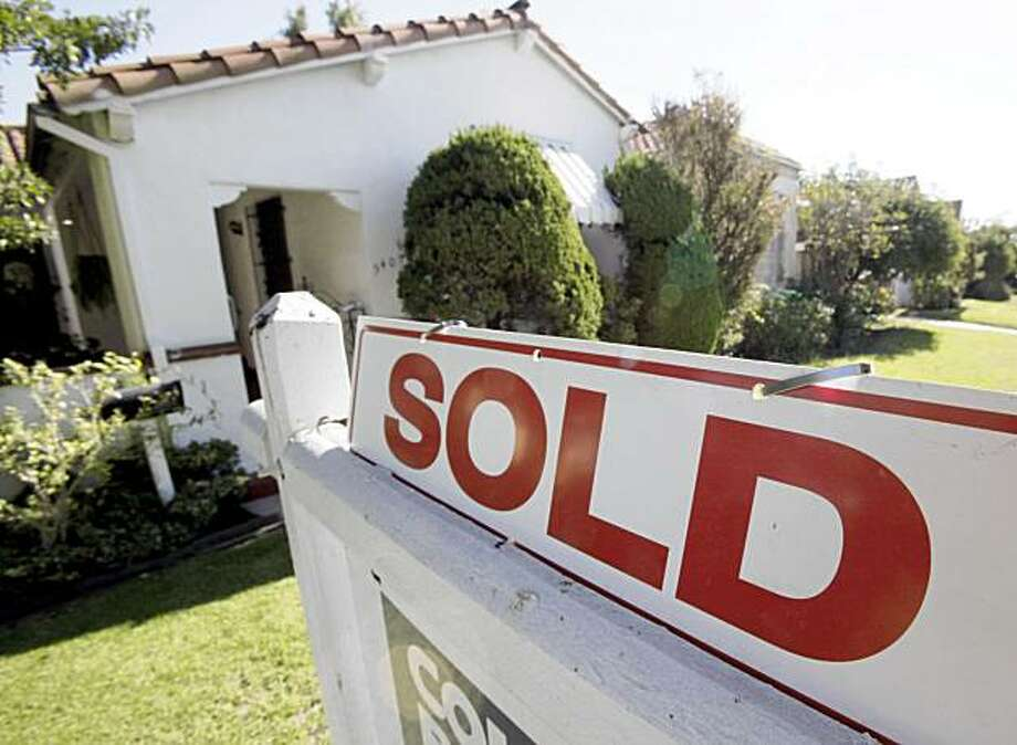 "In this Nov. 17, 2009 photo, A ""sold"" sign is seen outside a home in Los Angeles. October home sales are up 10.1 percent, beating expectations, as tax credit spurs sales. (AP Photo/Reed Saxon) Photo: Reed Saxon, AP"