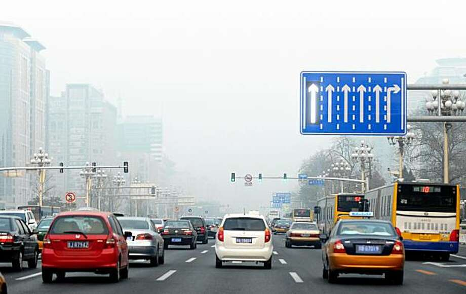 An arrow on a traffic road sign is illuminated as vehicles travel along the central east-west axis of Chang'An Avenue in Beijing on a smoggy day on November 26, 2009. China said it will cut the intensity of carbon dioxide emissions per unit of gross domestic product in 2020 by 40 to 45 percent from 2005 levels, offering targets for the first time. China and the United States are the world's number one and two sources of greenhouse gases and are considered critical to any progress at Copenhagen. AFP PHOTO/Frederic J. BROWN (Photo credit should read FREDERIC J. BROWN/AFP/Getty Images) Photo: Frederic J. Brown, AFP/Getty Images