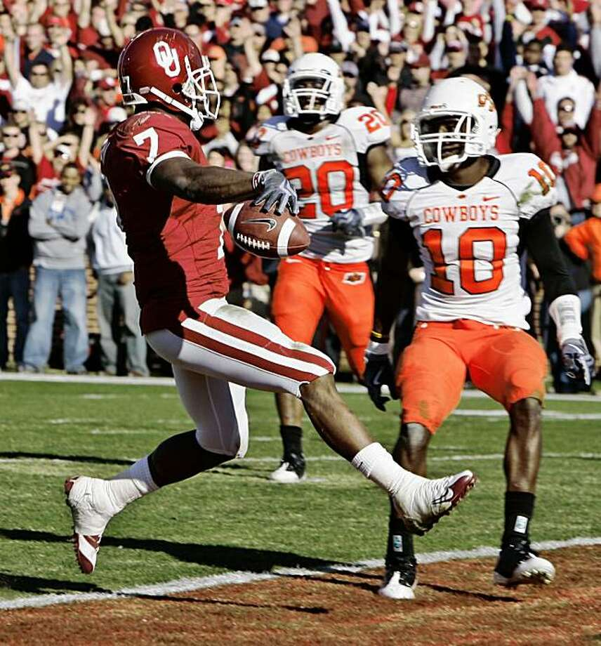 Oklahoma running back DeMarco Murray, left, jumps into the end zone with a touchdown in front of Oklahoma State linebacker Andre Sexton, center, and safety Markelle Martin, right, in the third quarter of an NCAA college football game in Norman, Okla., Saturday, Nov. 28, 2009. Murray ran for two touchdowns, as Oklahoma knocked No. 11 Oklahoma State out of contention for its first appearance in the Bowl Championship Series with a 27-0 win. (AP Photo/Sue Ogrocki) Photo: Sue Ogrocki, AP