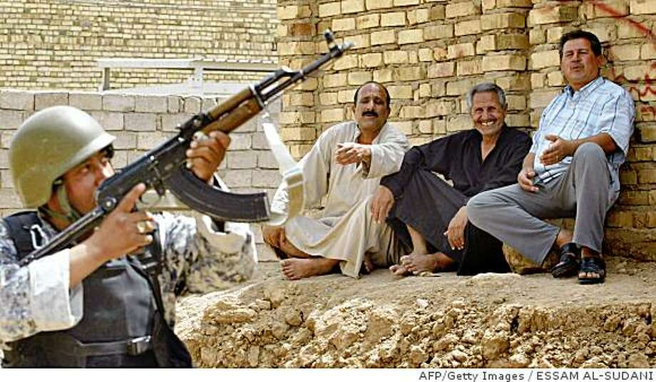 Iraqi men laugh and gesture as an Iraqi policeman he aims his assault rifle in the southern city of Amara in Maysan province, 365 kilometres south of Baghdad, on June 19, 2008. Iraqi forces backed by US troops launched a new operation against Shiite fighters in the south of the country early today after the expiry of a four-day deadline to surrender arms. AFP PHOTO/ESSAM AL-SUDANI (Photo credit should read ESSAM AL-SUDANI/AFP/Getty Images) Photo: ESSAM AL-SUDANI, AFP/Getty Images