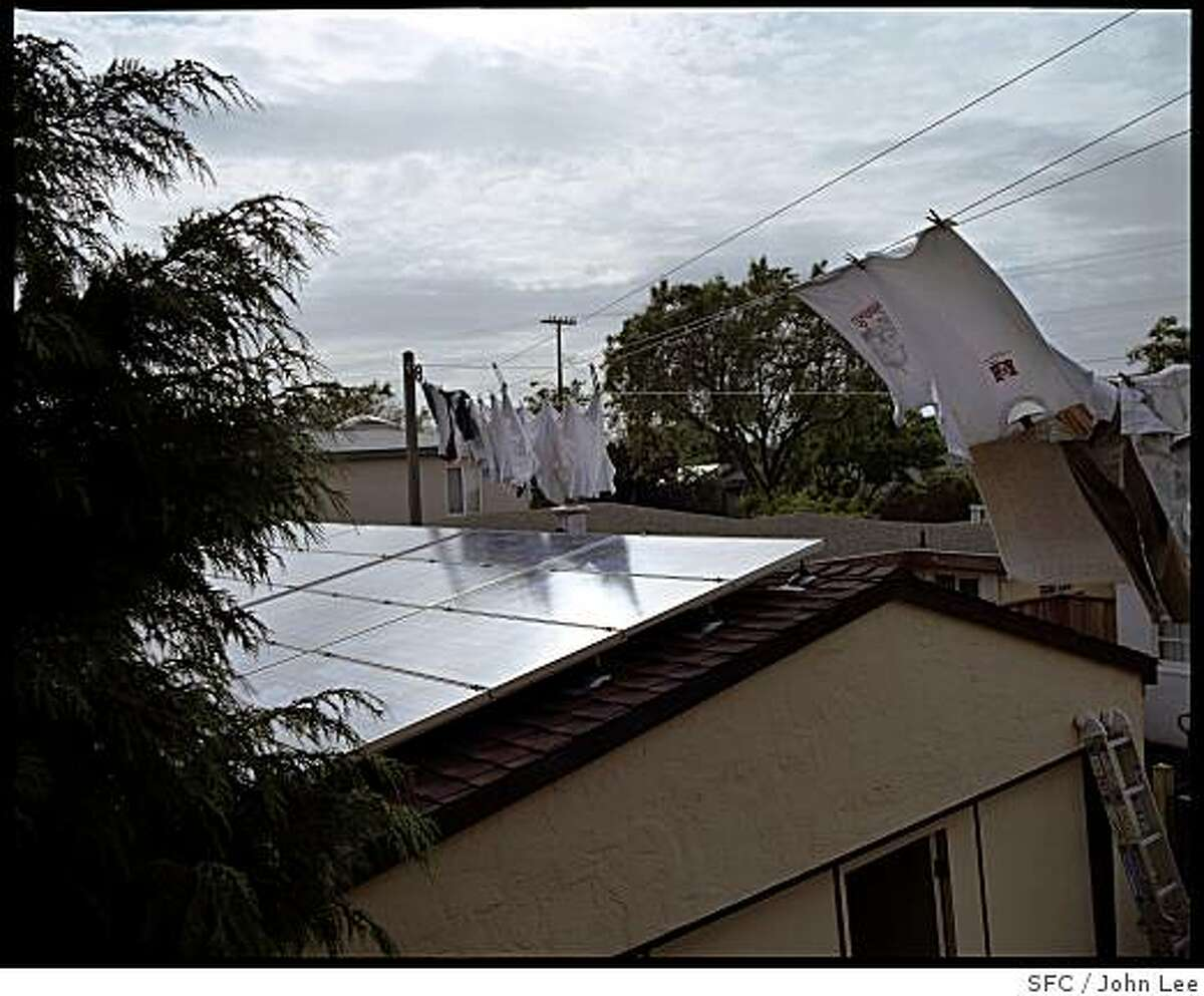MAG_GREEN22_14_JOHNLEE.JPG BERKELEY, CA - MAY 24: A bank of solar panels are mounted on the roof of the garage at Steve Greenberg's (cq) and Liz Varnhagen's (cq) Berkeley home. A clothesline with laundry drying blows above. For Sam Whiting story.BY JOHN LEE / SPECIAL TO THE CHRONICLE