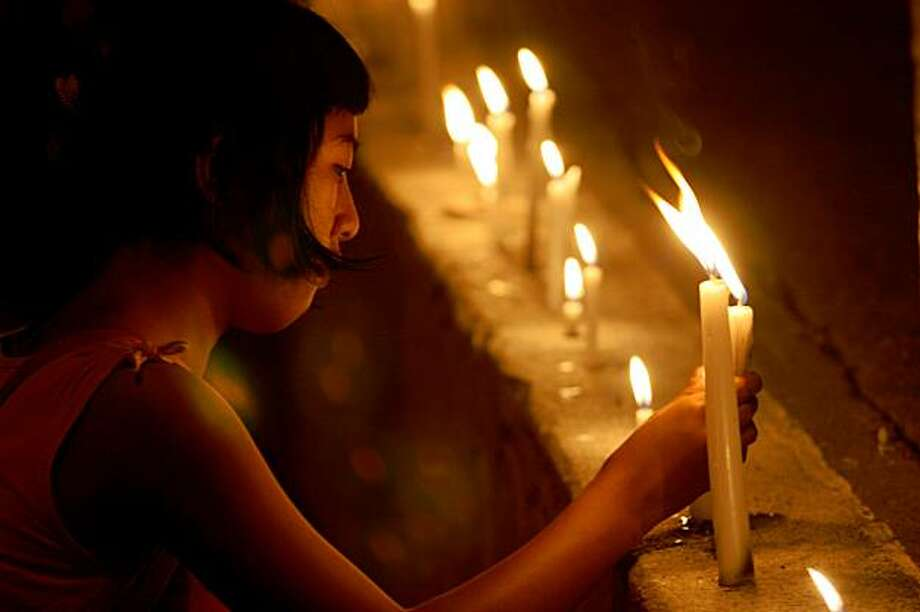 MAGUINDANAO PROVINCE, PHILIPPINES - NOVEMBER 24:  Families, friends, students and sympathizers light candles for those who died during a politically motivated massacre in nearby Ampatuan town yesterday, on  November 25, 2009 in the southern city of Koronadal, Philippines. President Gloria Macapagal-Arroyo vowed to hunt down the 100 gunmen reported to have hijacked a party of 30-40 people en route to filing election papers for candidate Mangudadatu ahead of next May's elections. Mangudadatu's wife, sister and family members, Armed Forces of the Philippines, civilians and at least 12 media personnel are thought to be amongst those killed in the attack, believed to be politically motivated. The Ampatuan clan, political rivals, are being blamed for the kidnap, mutilation, rape and murder of the victims.  (Photo by Jeoffrey Maitem/Getty Images) Photo: Jeoffrey Maitem, Getty Images