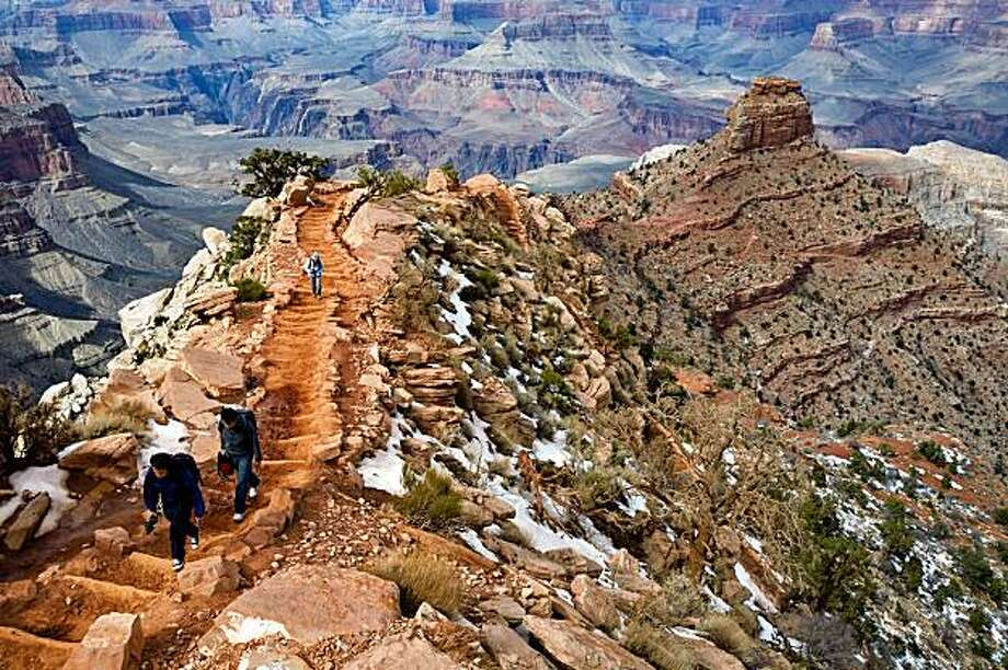 *FILE PHOTO* -- Hikers coming up out of the Grand Canyon on the South Kaibab trail, headed for the South Rim in Grand Canyon National Park, Ariz., in February 2009. To experience the Grand Canyon, you have to leave the rim. The frustration aroused by the bigness, the grandness, on a rim-only visit becomes a liberation once you drop down. The modern world falls away. ItÕs not just a trip out of the human realm, but into the deep geology of the earth. (Richard Perry/The New York Times) Photo: Richard Perry, NYT