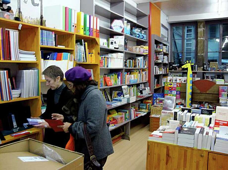 FRANCE BOOKS: Corinne Dalloz helps a customer in a bookshop in Poligny, France, that was on the verge of closing until it was bought by local residents. Illustrates FRANCE-BOOKS (category i), by Edward Cody (c) 2009, The Washington Post. Moved Monday, Nov. 16, 2009. (MUST CREDIT: Washington Post photo by Edward Cody.)  Corinne Dalloz helps a customer in a bookshop in Poligny, France, that was on the verge of closing until it was bought by local residents. Illustrates FRANCE-BOOKS (category i), by Edward Cody (c) 2009, The Washington Post. Moved Monday, Nov. 16, 2009. (MUST CREDIT: Washington Post photo by Edward Cody.) Photo: Edward Cody, Washington Post