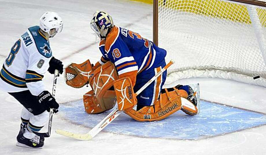 San Jose Sharks' Joe Pavelski, left, scores the overtime shootout winning goal on the Edmonton Oilers' Jeff Deslauriers in overtime of an NHL hockey game in Edmonton, Alberta, on Friday, Nov. 27, 2009. (AP Photo/The Canadian Press, John Ulan) Photo: John Ulan, AP