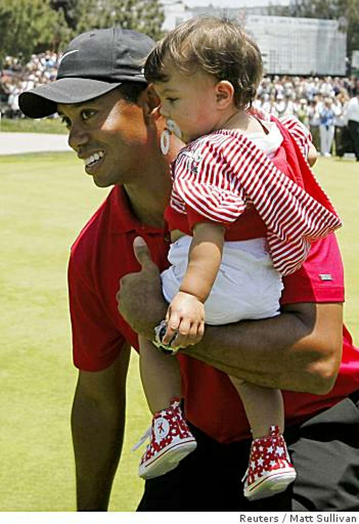 Tiger Woods walks with his daughter Sam Alexis after winning U.S. Open in a playoff at Torrey Pines in San Diego June 16, 2008.