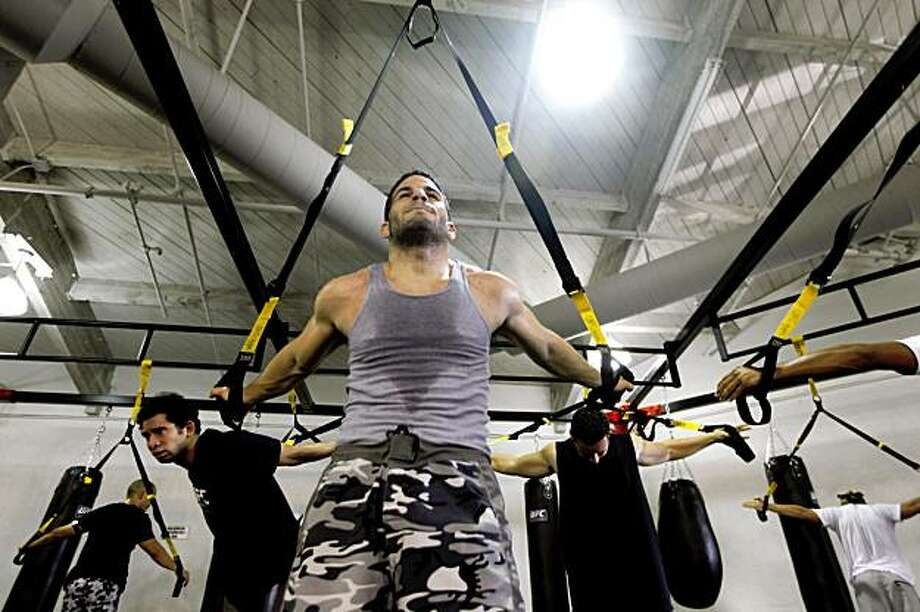 Onur Yenigun from Walnut Creek Ca, uses a TRX Suspension Trainer along with other students during their one-hour class thought by Tanya Merryman the gyms lead instructor. The Ultimate Fighting Championship, a mixed-Martial arts group, has opened their first gym in Concord. UFC gym hopes to attract a wide verity of fitness enthusiasts as well as families. Wednesday November 25, 2009. Photo: Lance Iversen, The Chronicle