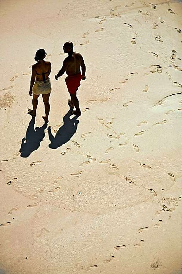 Couple walking on the beach near the Crane resort on the Atlantic coast of Barbados. Photo: Chris Hardy, Special To The Chronicle