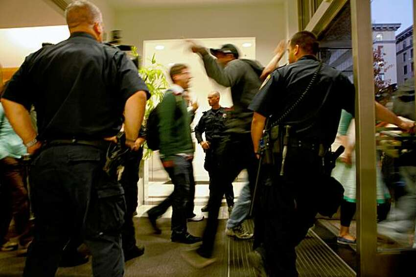 Students continue to yells as they walk through the police outside the University of California Administration Building, to protest in the streets, Monday Nov. 23, 2009, in Oakland, Calif