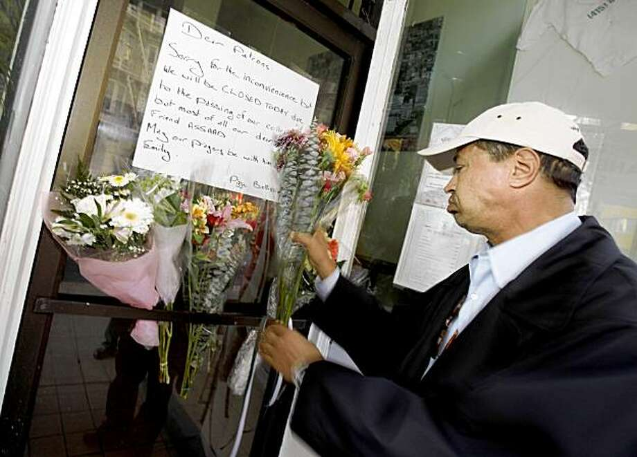 Marcel Douihech, a good friend of Assaad,  took flowers to the door of the restaurant which had closed for the day in memory of the slain worker. A worker named Assaad at Bellissimos Pizza on Sutter Street in San Francisco was stabbed to death early Tuesday morning at the restaurant. Photo: Brant Ward, The Chronicle