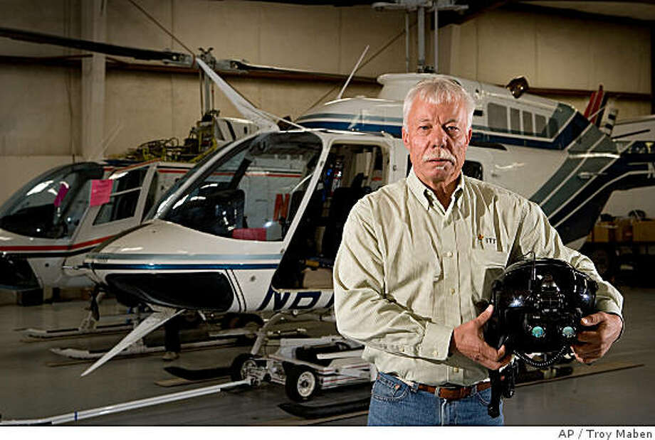 Mike Atwood, owner of Aviation Specialties Unlimited, Inc., holds a flight helmet, with night vision goggles attached, inside the hanger at his company's headquarters in Boise, Idaho, Tuesday, May 20, 2008. Atwood's company is a distributor of night vision goggles and says due to wars in Iraq and Afghanistan there is a shortage of goggles available to American medical pilots. (AP Photo/Troy Maben) Photo: Troy Maben, AP