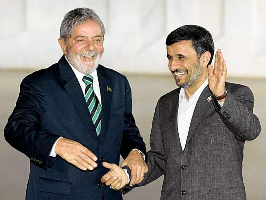 Iran's President Mahmoud Ahmadinejad, right, waves as he stands with Brazil's President Luiz Inacio Lula da Silva at the Itamaraty palace in Brasilia, Monday, Nov. 23, 2009. Ahmadinejad is on a one-day visit to Brazil. (AP Photo/Eraldo Peres) Photo: Eraldo Peres, AP