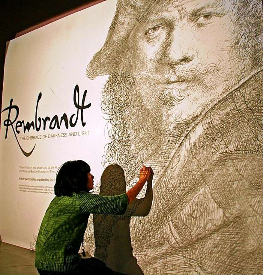 Nevada Museum of Art's Rembrandt show.    The picture shows a museum staffer using charcoal to trace a projection of a Rembrandt self portrait on the wall at the museum that will serve as the introduction to the show.  (Part of the projection is slightly visible on her back.) Photo: Mark S. Bacon