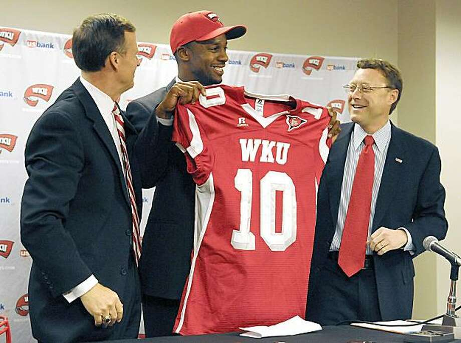 Western Kentucky's new football coach, Willie Taggart, holds up a WKU football jersey Monday, Nov. 23, 2009, in Bowling Green, Ky., flanked by university president Gary Ransdell, left, and athletic director Wood Selig. Taggart has spent the past three seasons as running backs coach at Stanford. Prior to that, Taggart spent eight years as an assistant at WKU under former coach Jack Harbaugh and recently fired coach David Elson. (AP Photo/Daily News, Joe Imel) Photo: Joe Imel, AP