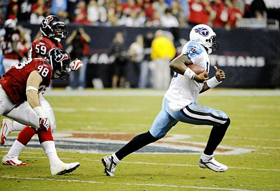 Tennessee Titans quarterback Vince Young (10) races upfield followed by Houston Texans' Connor Barwin (98) and DeMeco Ryans (59) during the third quarter of an NFL football game Monday, Nov. 23, 2009, in Houston. (AP Photo/Dave Einsel) Photo: Dave Einsel, AP