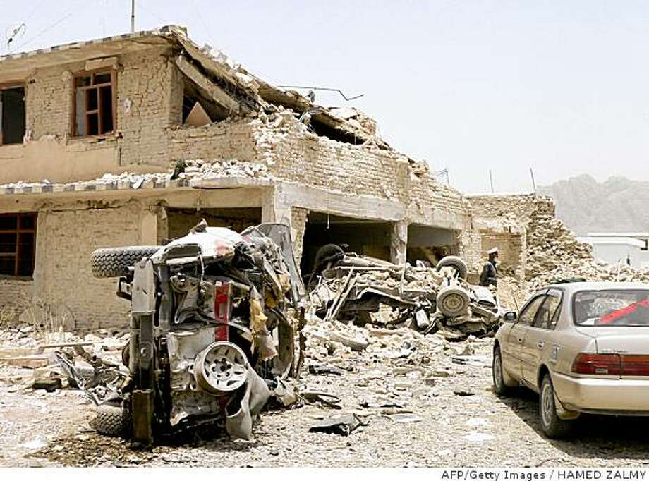 An Afghan policeman stands among shattered buildings and vehicles at the site of a suicide attack in front of the entrance to the main jail in Kandahar on June 14, 2008. Taliban rebels blasted into a prison using a suicide car bomb and guns late June 13, freeing as many as hundreds of militant prisoners and killing at least two guards, officials said. The brazen attack under cover of darkness ripped through the front entrance of the main jail in the insurgency-hit southern city of Kandahar, Justice Minister Sarwar Danish told AFP.   AFP PHOTO/Hamed ZALMY (Photo credit should read HAMED ZALMY/AFP/Getty Images) Photo: HAMED ZALMY, AFP/Getty Images