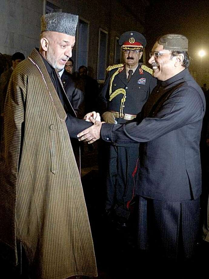 Newly reelected Afghan President Hamid Karzai (L) shakes hands with Pakistan President Asif Ali Zardari during a meeting at the Presidential palace in Kabul on November 18, 2009. Zardari arrived in Afghanistan to attend on November 19 the investiture ceremony for Karzai. The 51-year-old is due to be sworn in for a second mandate at his heavily fortified palace following the controversial August ballot. AFP PHOTO / POOL / Musadeq Sadeq (Photo credit should read MUSADEQ SADEQ/AFP/Getty Images) Photo: Musadeq Sadeq, AFP/Getty Images