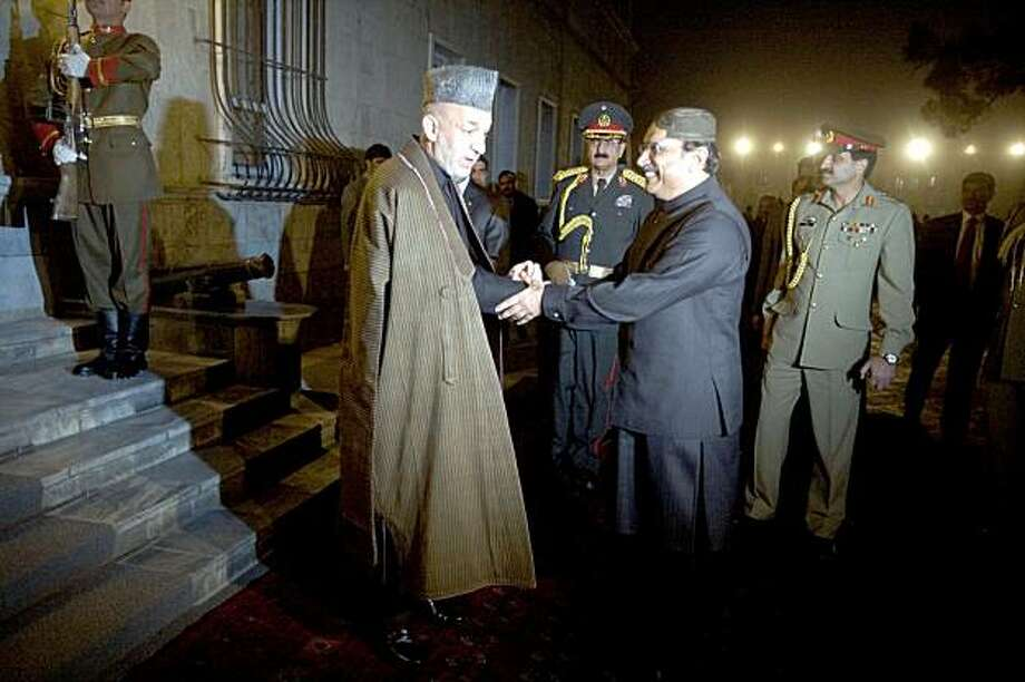 KABUL, AFGHANISTAN - NOVEMBER 18:  Afghan President Hamid Karzai (L) shakes hands with Pakistan President Asif Ali Zardari at the presidential palace on November 18, 2009 in Kabul, Afghanistan. Zardari arrived in Afghanistan to attend Thursday's inauguration of Afghan President Hamid Karzai. (Musadeq Sadeq-Pool/Getty Images)) Photo: Pool, Getty Images