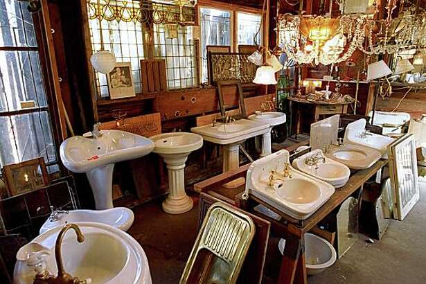 Pedestal sinks, stained glass windows and lighting fixtures at Omega Salvage in Berkeley.