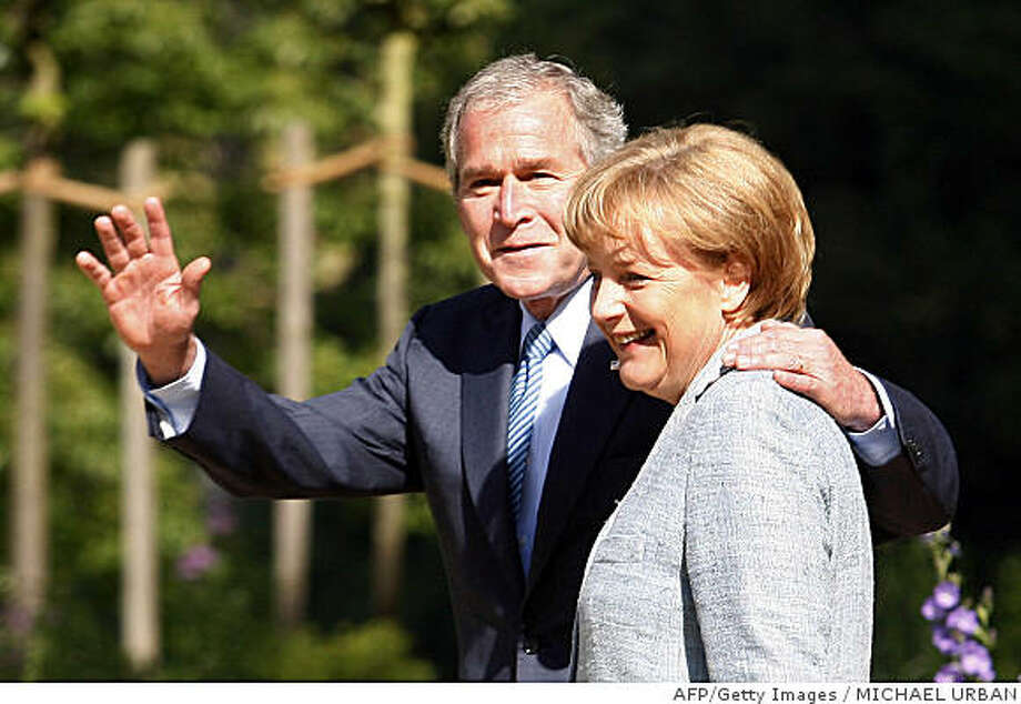 US President George W. Bush (L) waves as he and German Chancellor Angela Merkel walk through the garden of the guesthouse of the German government, the Meseberg Palace, north of Berlin, on June 11, 2008. President Bush and German Chancellor Angela Merkel met for talks to be dominated by the Iranian nuclear programme, climate protection and transatlantic trade. Germany is the second stop on a farewell tour of Europe before Bush leaves office in January 2009.                    AFP  PHOTO DDP / MICHAEL URBAN  GERMANY OUT (Photo credit should read MICHAEL URBAN/AFP/Getty Images) Photo: MICHAEL URBAN, AFP/Getty Images