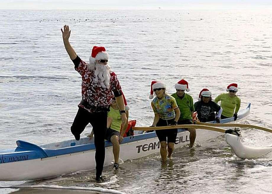 Surfing Santa in Capitola. Photo: Santa Cruz County CVC, Covello & Covello
