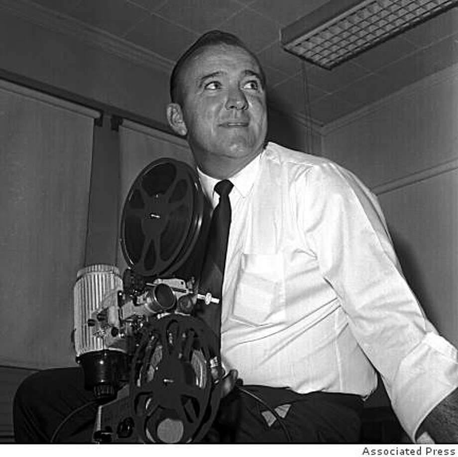 **FILE** In this April 1966 file photo, John Rauch watches films after being named head football coach of the Oakland Raiders in Oakland, Calif. Rauch, the former Georgia quarterback who coached the Raiders to a berth in the second Super Bowl, died Tuesday, June 10, 2008, at his home in Oldsmar, Fla. He was 80. (AP Photo) Photo: Associated Press, AP
