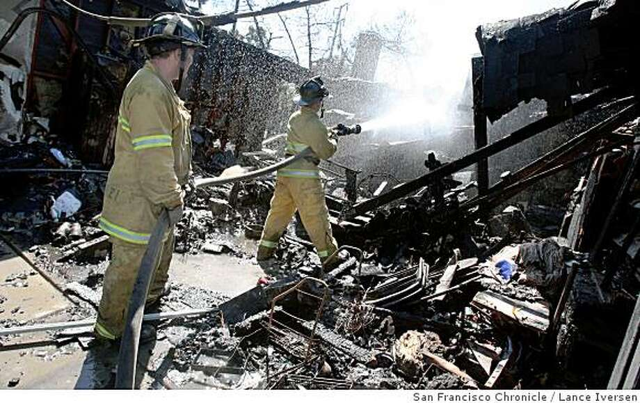 Stockton firefighters knock down hot spots in a garage of a home on Rock Creek Court Tuesday June 10, 2008. A wind fed brush fire has destroyed seven single-family homes, a condo complex, and dozens of trees along Highway #5 at March Lane in Stockton.  Photo by Lance Iversen / The Chronicle Photo: Lance Iversen, San Francisco Chronicle