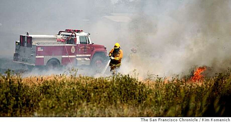 Contra Costa County firefighters help put out a fire that burned more than 20 acres of pasture along Arthur Road near Martinez, Calif. on Tuesday, June10, 2008.Photo by Kim Komenich / The Chronicle Photo: Kim Komenich, The San Francisco Chronicle