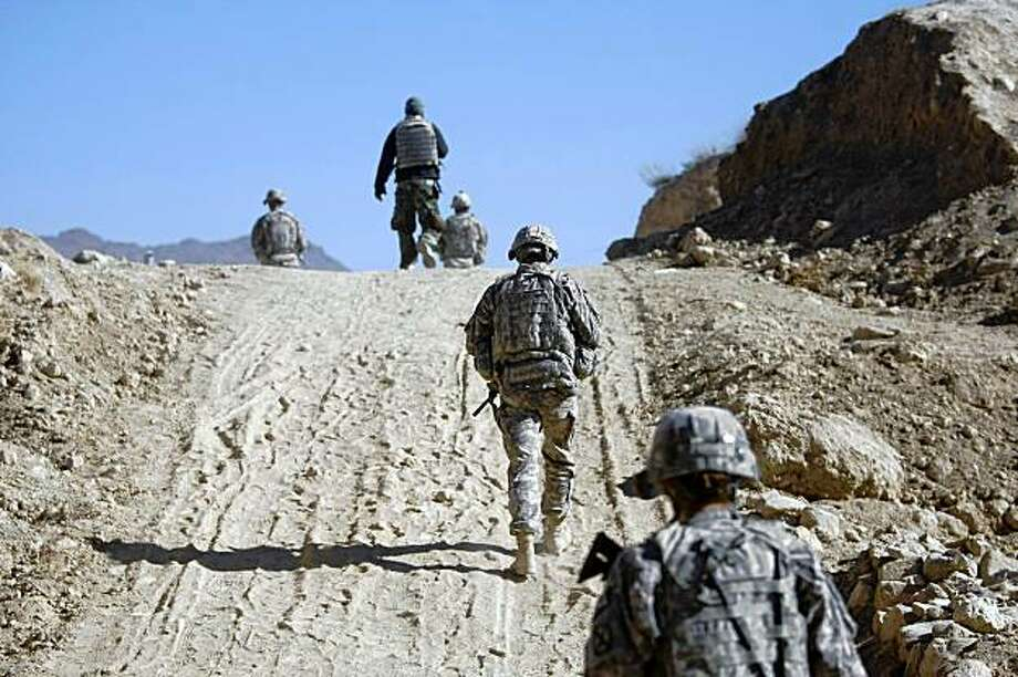 U.S. soldiers from the 3rd Brigade Special Troops Battalion walk on a dirt road while on patrol near the town of Pul-i-alam, Logar province, Afghanistan, Wednesday, Nov. 18, 2009. (AP Photo/Dario Lopez-Mills) Photo: Dario Lopez-Mills, AP