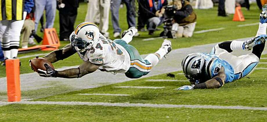 Miami Dolphins' Ricky Williams (34) stretches the ball over the goal line for a touchdown as Carolina Panthers' Jon Beason (52) falls in the first half of an NFL football game in Charlotte, N.C., Thursday, Nov. 19, 2009. (AP Photo/Chuck Burton) Photo: Chuck Burton, AP